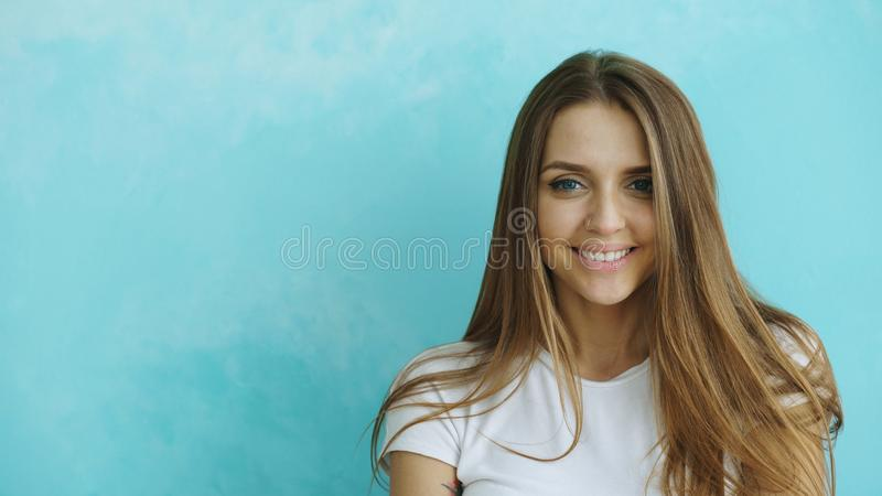 Ritratto del primo piano di giovane donna sorridente e di risata che esamina macchina fotografica su fondo blu fotografia stock