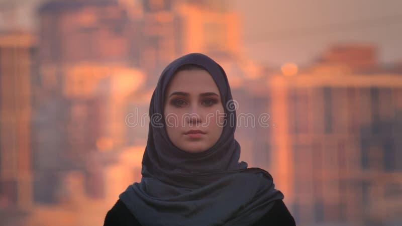 Ritratto del primo piano di giovane femmina attraente nel hijab che esamina diritto la macchina fotografica con la città urbana s immagine stock libera da diritti