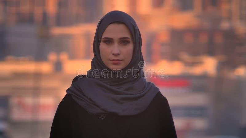 Ritratto del primo piano di giovane femmina attraente nel hijab che esamina diritto la macchina fotografica con l'ambiente urbano fotografia stock libera da diritti