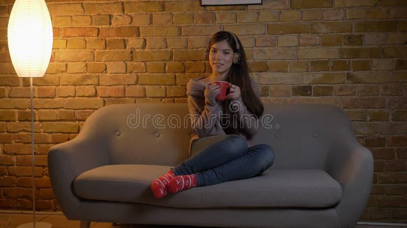 Ritratto del primo piano di giovane femmina caucasica che ascolta la musica in cuffie mentre sedendosi sullo strato e tenendo una fotografia stock libera da diritti