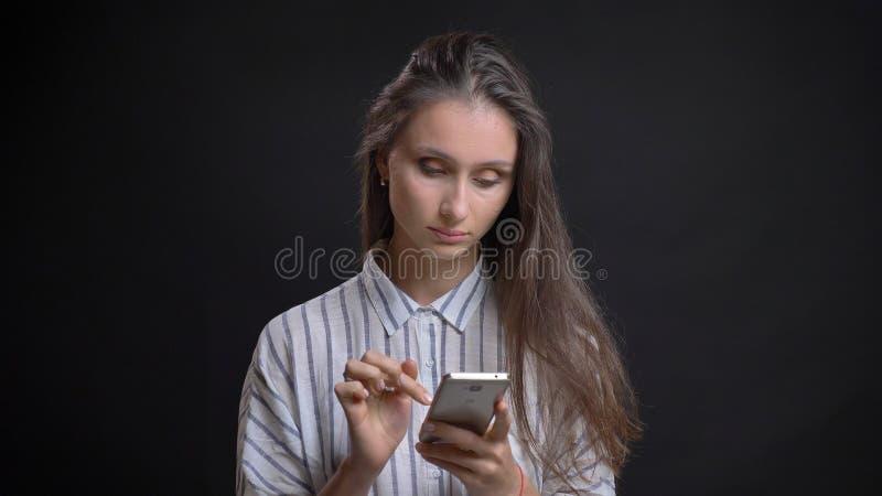 Ritratto del primo piano di giovane femmina caucasica sveglia facendo uso del telefono davanti alla macchina fotografica con fond immagine stock