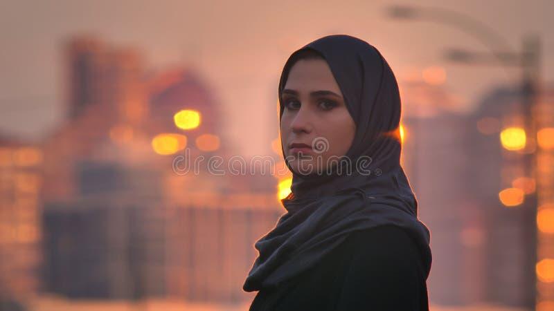 Ritratto del primo piano di giovane femmina graziosa nel hijab che gira e che esamina macchina fotografica con le costruzioni bri fotografie stock libere da diritti