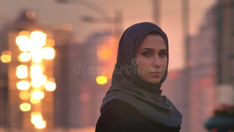 Ritratto del primo piano di giovane femmina graziosa nel hijab che gira e che esamina macchina fotografica con le costruzioni bri immagini stock