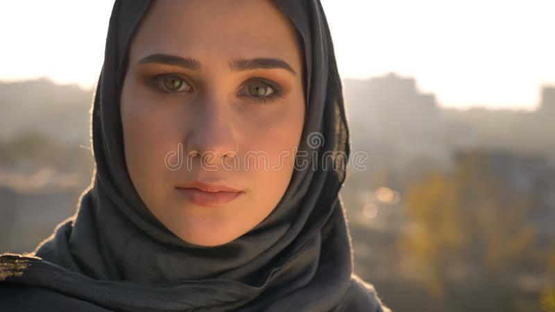 Ritratto del primo piano di giovane femmina musulmana attraente nel hijab che guarda diritto con l'ambiente urbano sui precedenti fotografia stock libera da diritti