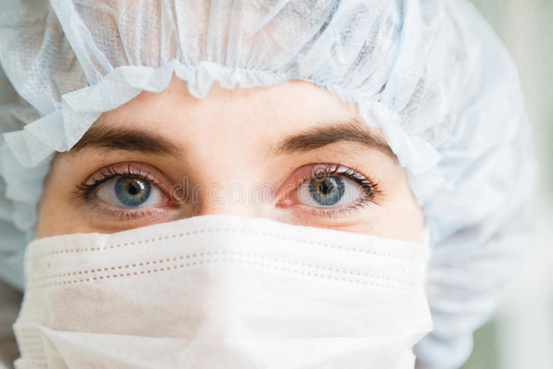 Ritratto del primo piano di giovane medico o interno femminile del chirurgo che porta maschera protettiva e cappello fotografia stock libera da diritti