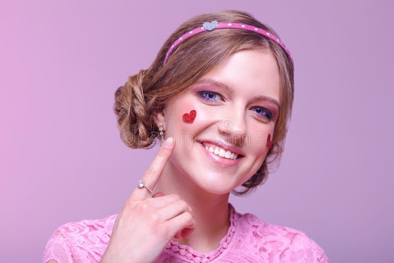 Ritratto del primo piano di giovane ragazza positiva con trucco di ogni giorno professionale in tonalità rosa con un orlo e nei c fotografie stock