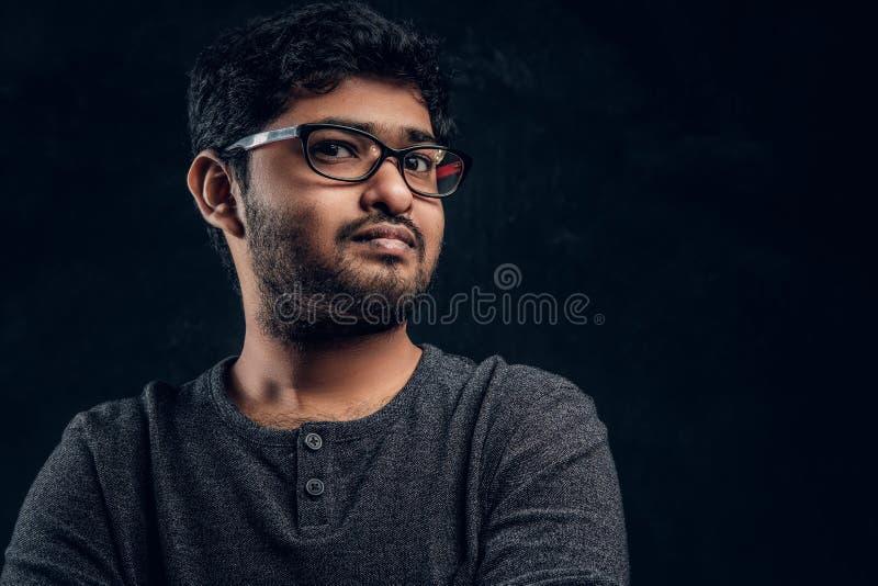 Ritratto del primo piano di giovane tipo indiano in occhiali e abbigliamento casual che esamina una macchina fotografica in studi fotografia stock libera da diritti