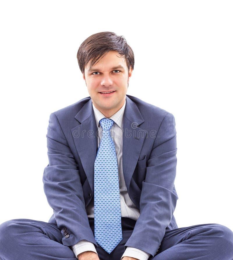 Ritratto del primo piano di giovane uomo d'affari che si siede a gambe accavallate immagine stock libera da diritti