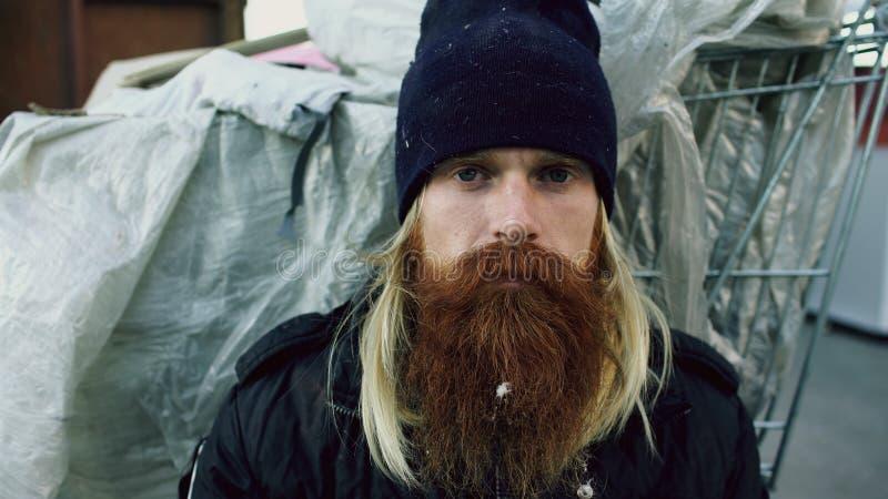Ritratto del primo piano di giovane uomo senza tetto barbuto che si siede su un marciapiede vicino al contenitore dell'immondizia fotografia stock