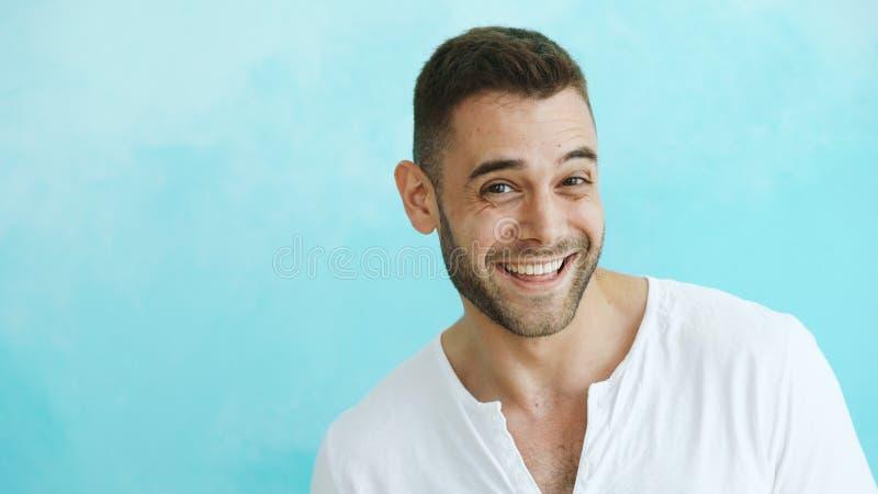 Ritratto del primo piano di giovane uomo sorridente e di risata che esamina macchina fotografica su fondo blu immagine stock libera da diritti