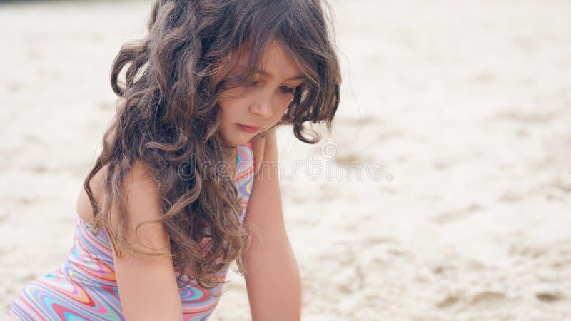 Ritratto del primo piano di ragazza ispana abbastanza piccola con l'ondeggiamento nei capelli lunghi del vento che si siedono sul fotografia stock libera da diritti