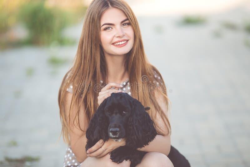 Ritratto del primo piano di ragazza teenager abbastanza giovane con il cane nero di cocker spaniel immagini stock libere da diritti