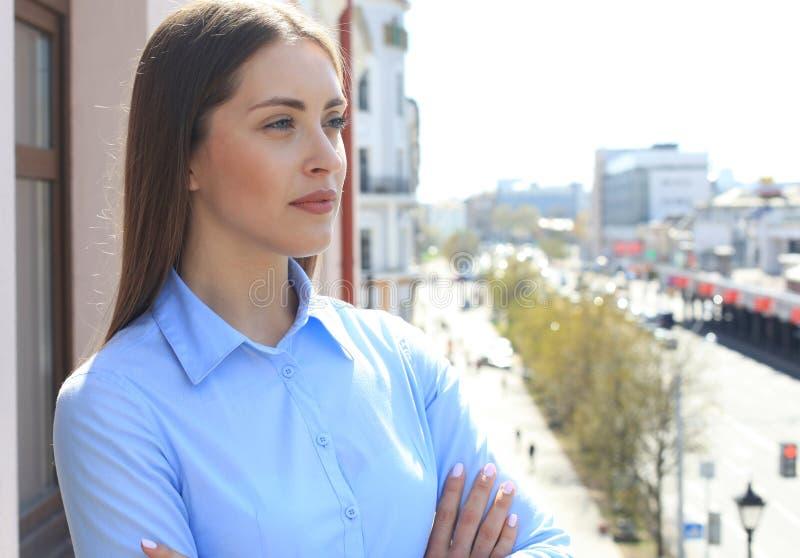 Ritratto del primo piano di rilassamento sulla donna di affari del balcone su fondo delle costruzioni della città fotografia stock libera da diritti
