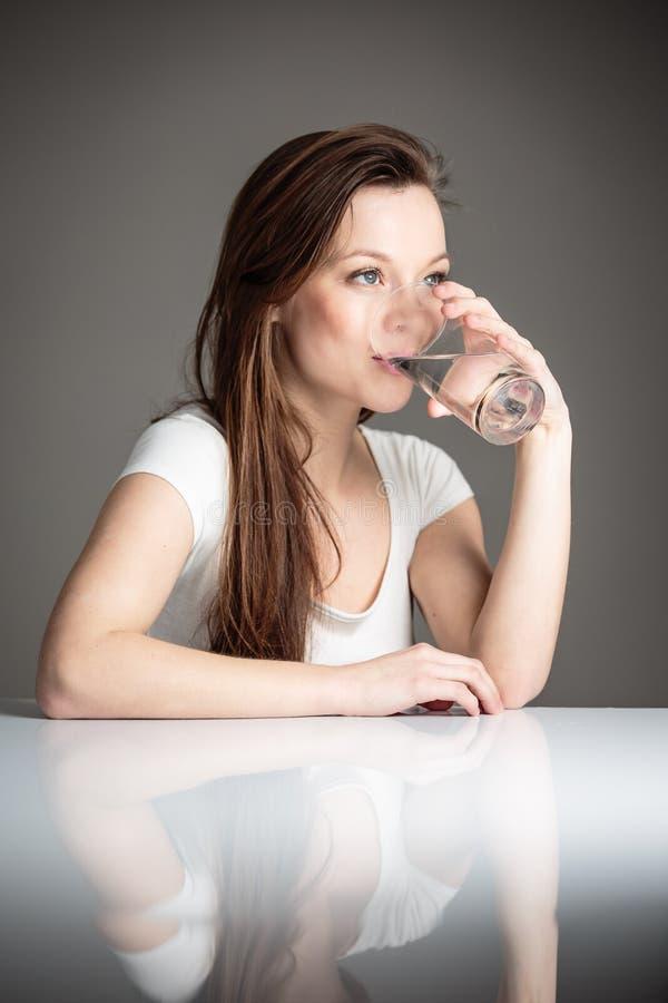 Ritratto del primo piano di un'acqua potabile della giovane donna attraente fotografia stock