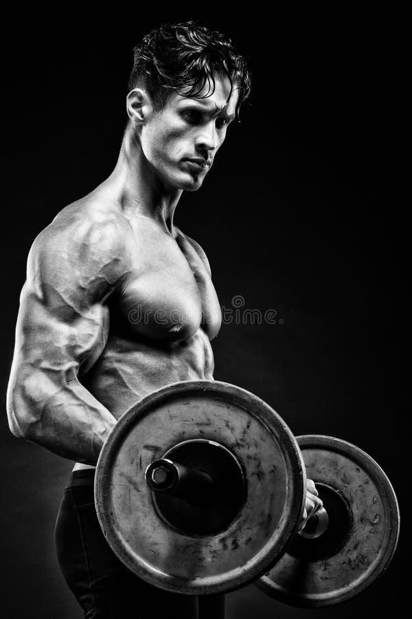 Ritratto del primo piano di un allenamento muscolare dell'uomo con il bilanciere alla palestra immagini stock libere da diritti