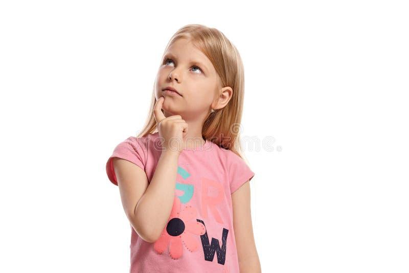 Ritratto del primo piano di un bambino biondo piacevole in una posa rosa della maglietta isolato su fondo bianco fotografie stock libere da diritti