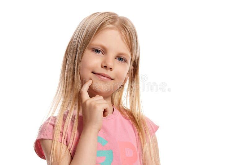 Ritratto del primo piano di un bambino biondo piacevole in una posa rosa della maglietta isolato su fondo bianco fotografie stock