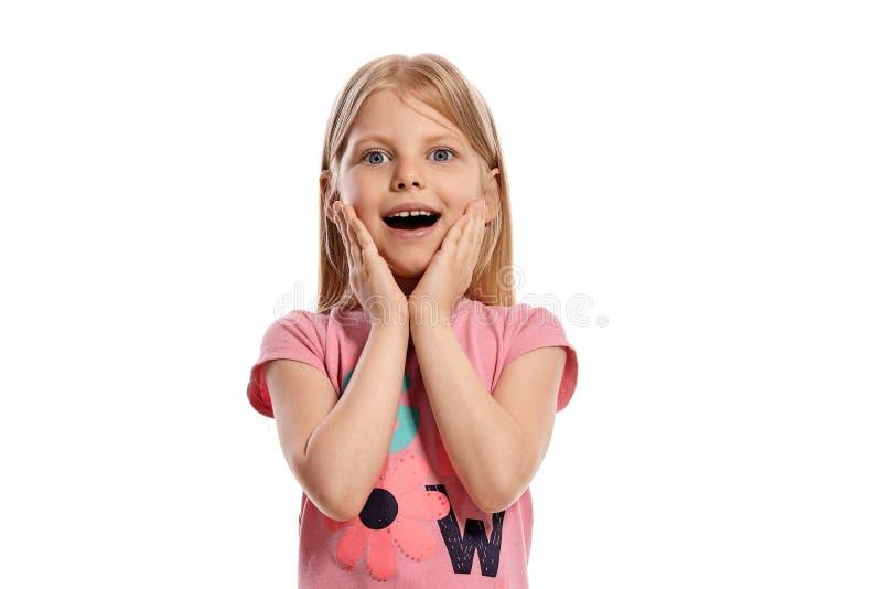 Ritratto del primo piano di un bambino biondo piacevole in una posa rosa della maglietta isolato su fondo bianco fotografia stock