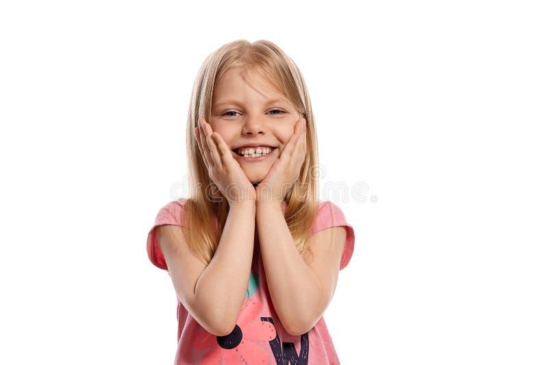 Ritratto del primo piano di un bambino biondo piacevole in una posa rosa della maglietta isolato su fondo bianco immagini stock