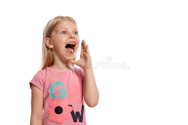 Ritratto del primo piano di un bambino biondo piacevole in una posa rosa della maglietta isolato su fondo bianco fotografia stock libera da diritti