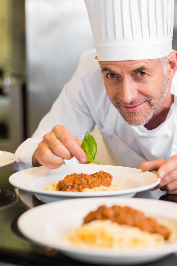 Ritratto del primo piano di un cuoco unico maschio che guarnisce alimento immagine stock libera da diritti