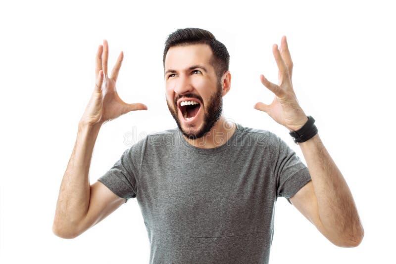 Ritratto del primo piano di un giovane con una barba, portante una maglietta grigia, con un'espressione irritata, gridante nella  fotografia stock libera da diritti