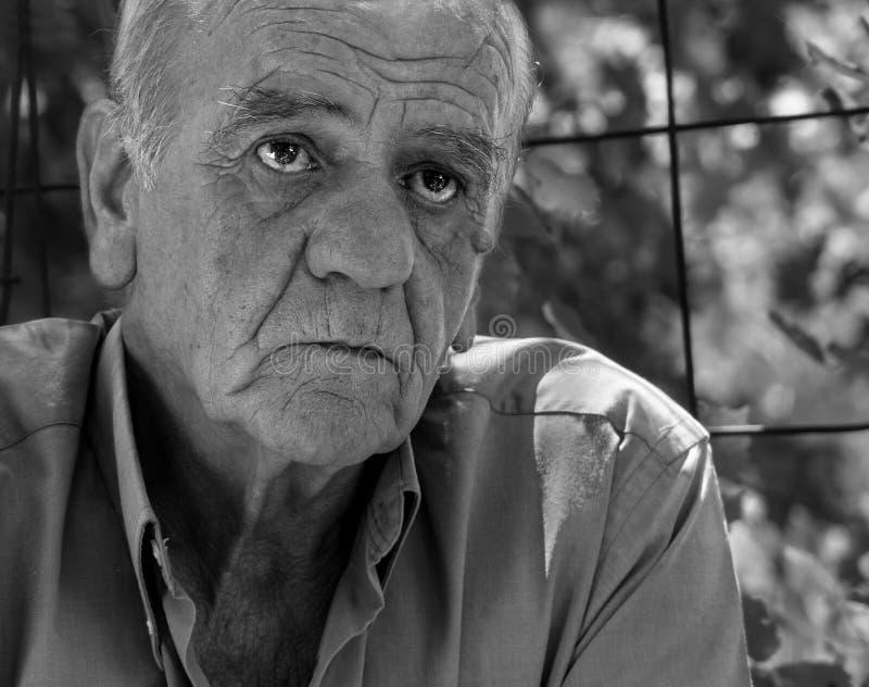 Ritratto del primo piano di un maschio pensionato greco anziano serio che fuma una sigaretta con un sorriso, in bianco e nero fotografia stock