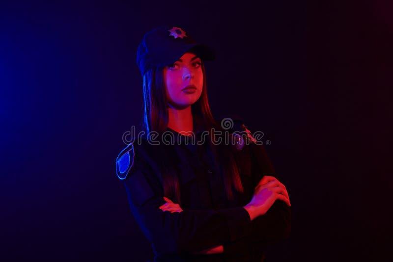 Ritratto del primo piano di un ufficiale di polizia femminile che posa per la macchina fotografica contro un fondo nero con rosso fotografia stock