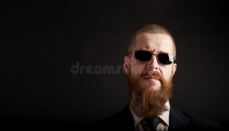 Ritratto del primo piano di un uomo d'affari barbuto in vetri neri con il posto per copia-pasta fotografie stock libere da diritti