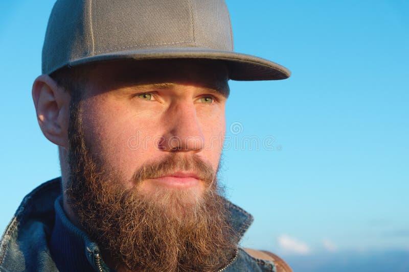 Ritratto del primo piano di un viaggiatore alla moda barbuto in un cappuccio contro un cielo blu Tempo di viaggiare concetto immagini stock