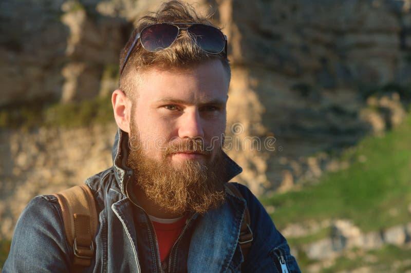 Ritratto del primo piano di un viaggiatore alla moda barbuto in un cappuccio contro le rocce epiche Tempo di viaggiare concetto fotografia stock