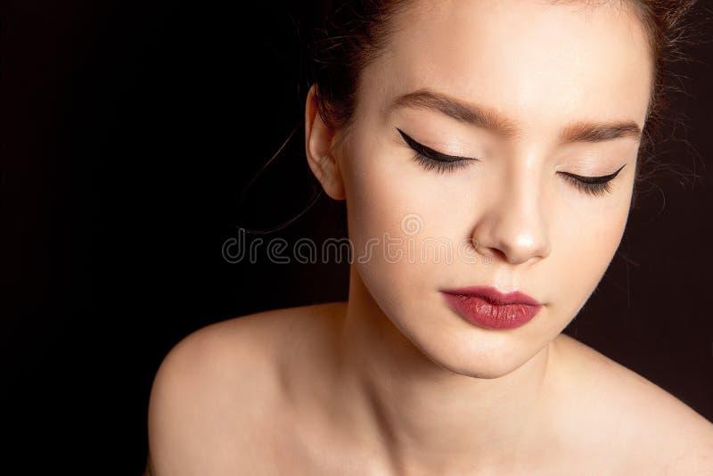 Ritratto del primo piano di una donna con trucco classico con una freccia nera e un labbro nudo sopra le sue spalle sul nero immagini stock libere da diritti
