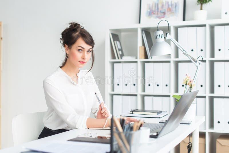 Ritratto del primo piano di una donna di affari nel suo luogo di lavoro che lavora con il pc, guardando in camera, vestito d'uso  fotografie stock libere da diritti