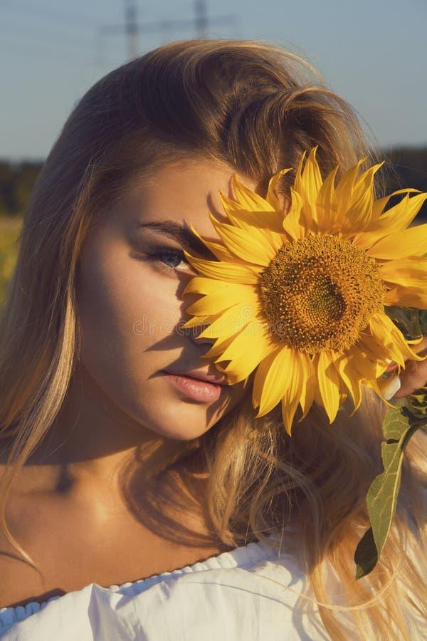 Ritratto del primo piano di una ragazza con un girasole fotografie stock