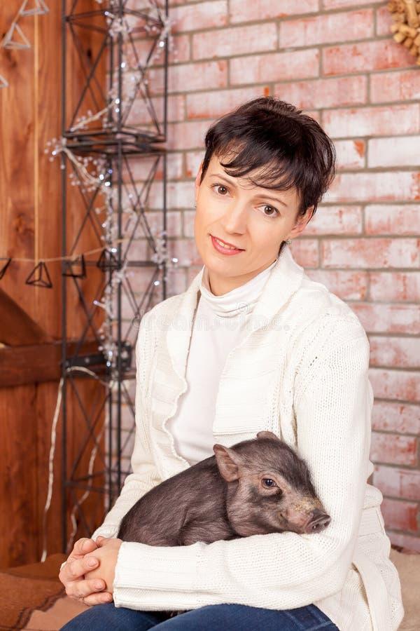 Ritratto del primo piano, donna felice e castana, impiegato della banca, abbracciante porcellino nero, simbolo cinese del nuovo a fotografia stock