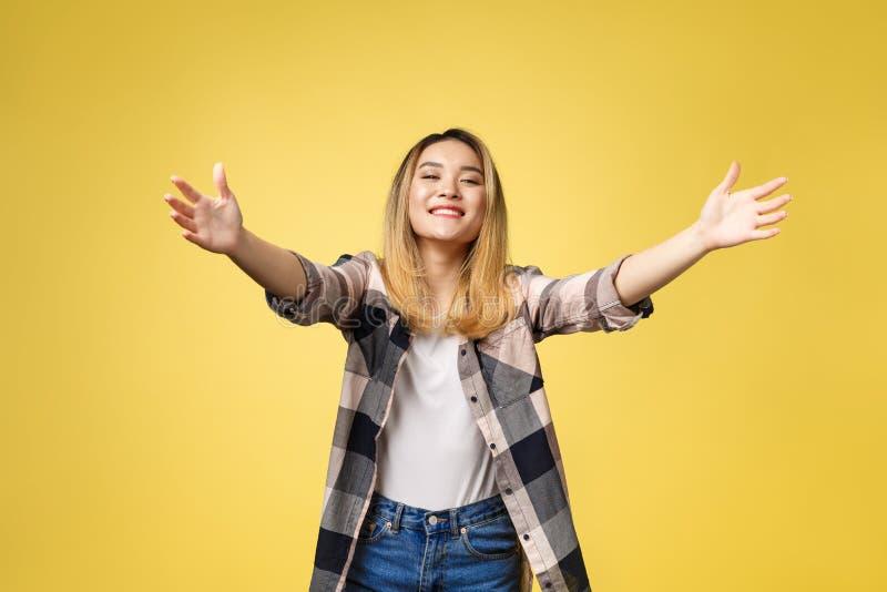 Ritratto del primo piano, giovane donna che fa segno con le armi per venire darle un abbraccio di orso, isolato su fondo giallo fotografie stock