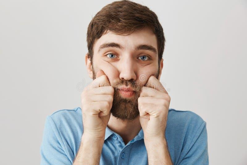 Ritratto del primo piano del maschio barbuto di ribaltamento triste, schiacciante le guance con le mani ed esaminante macchina fo fotografie stock libere da diritti