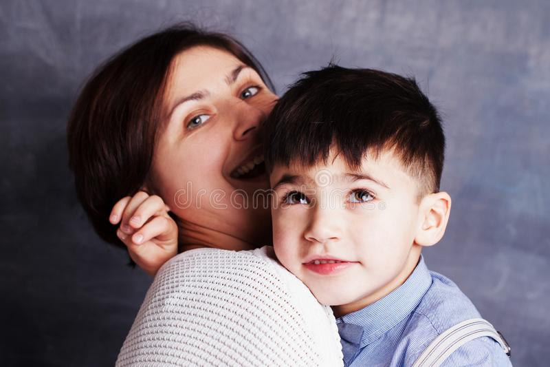 Ritratto del primo piano del ragazzino sveglio e della donna castana Madre e suo abbracciare del figlio fotografia stock