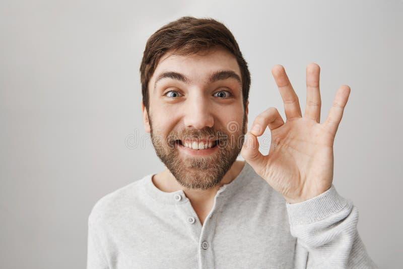 Ritratto del primo piano del tipo europeo divertente che mostra okay o del segno fine mentre sorridendo con l'eccitazione, essend immagine stock libera da diritti