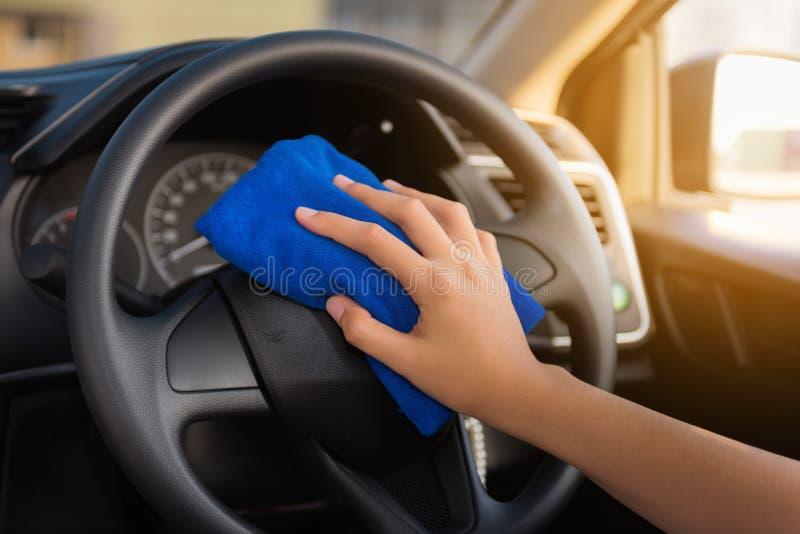 Ritratto del primo piano del volante dell'automobile di pulizia della mano della donna con immagine stock libera da diritti