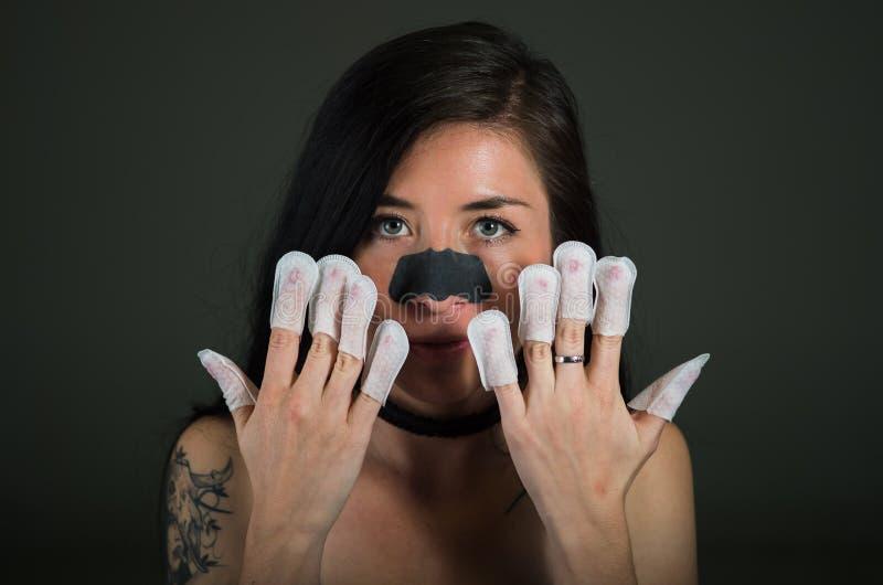 Ritratto del protettore d'uso delle unghie della giovane donna nelle sue unghie, mano e manicure pulito ideale, in un fondo nero fotografie stock