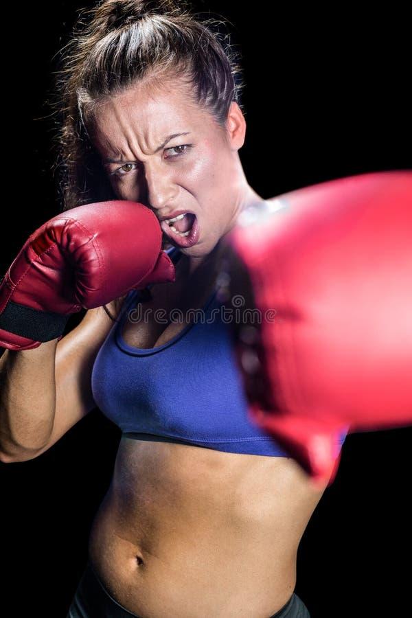 Ritratto del pugile femminile aggressivo con posizione di combattimento immagini stock libere da diritti