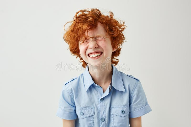 Ritratto del ragazzino allegro con i capelli e le lentiggini dello zenzero che ride fragorosamente con gli occhi chiusi in aula d fotografie stock libere da diritti