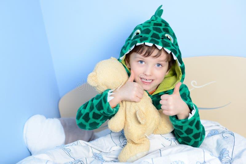 Ritratto del ragazzino che gesturing i pollici su con l'orsacchiotto a letto immagini stock