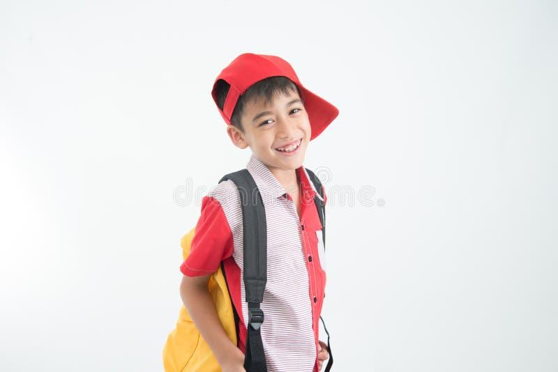 Ritratto del ragazzino che va a scuola con la cartella su bianco immagini stock libere da diritti