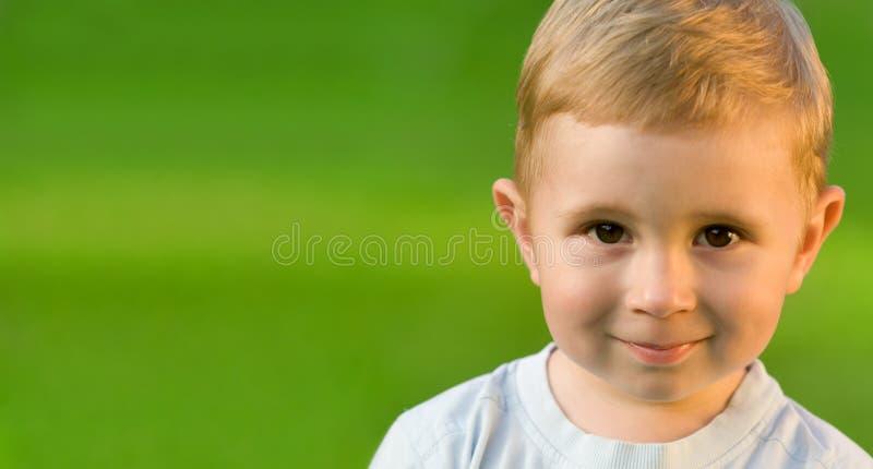 Ritratto del ragazzino sul campo di erba verde immagini stock libere da diritti