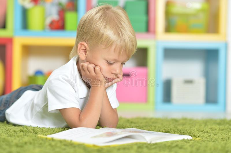 Ritratto del ragazzino sveglio che legge un libro mentre trovandosi sul pavimento immagine stock libera da diritti