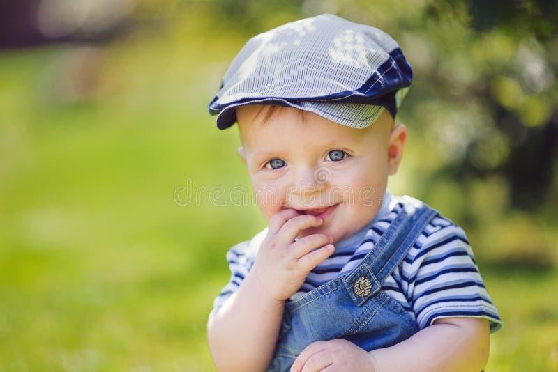 Ritratto del ragazzino sveglio che si siede sull'erba fotografia stock libera da diritti