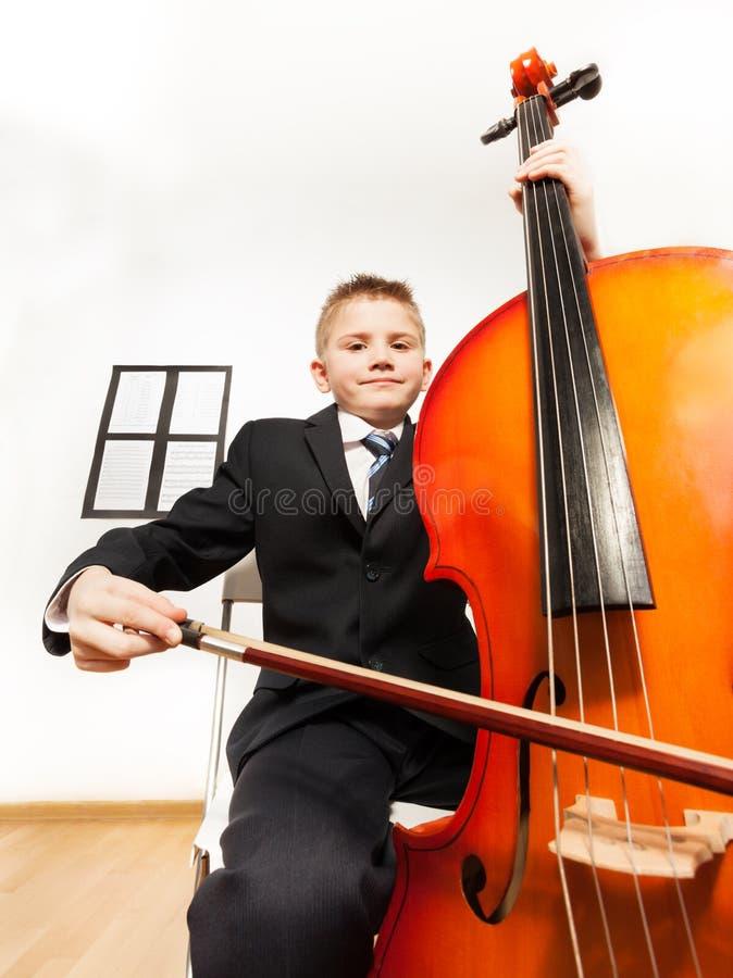 Ritratto del ragazzo che gioca violoncello che si siede sulla sedia fotografia stock