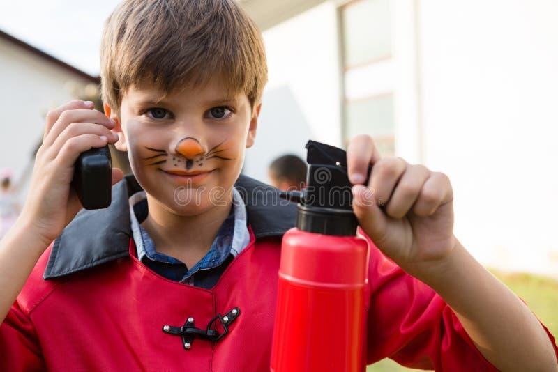Ritratto del ragazzo con la pittura del fronte facendo uso del walkie-talkie mentre estintore della tenuta fotografia stock libera da diritti